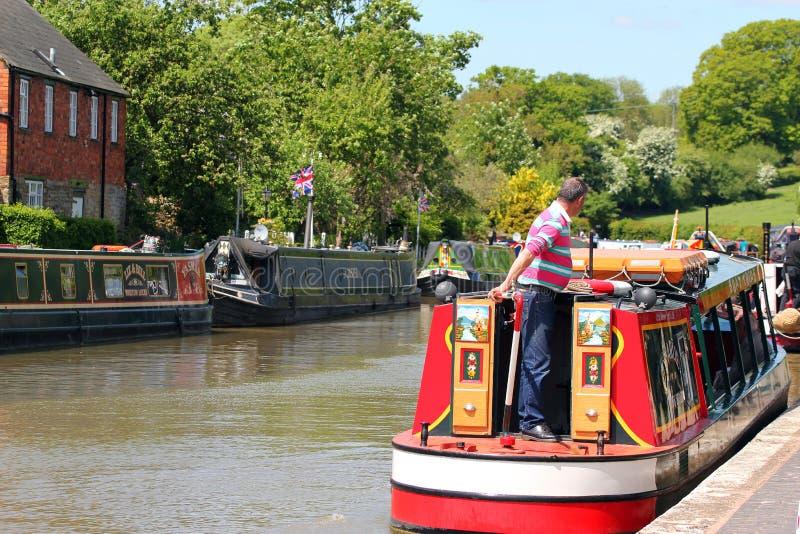 Homme conduisant une péniche ou un bateau étroit. photographie stock