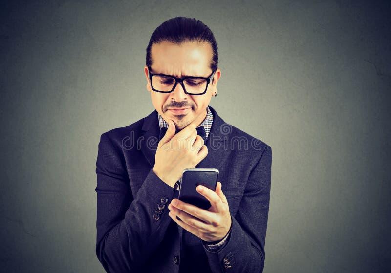 Homme confus ayant des problèmes avec le smartphone image libre de droits