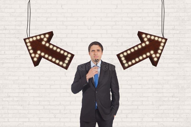 Homme confus d'affaires se tenant contre le mur blanc avec des flèches image stock