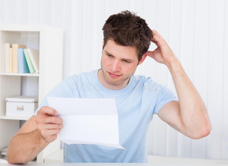 Homme confus regardant le papier photos libres de droits