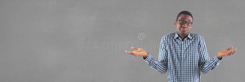 Homme confus se tenant contre le gris vide large image stock