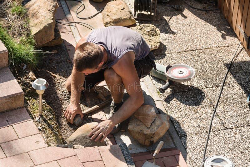 Homme construisant un mur de grès photographie stock