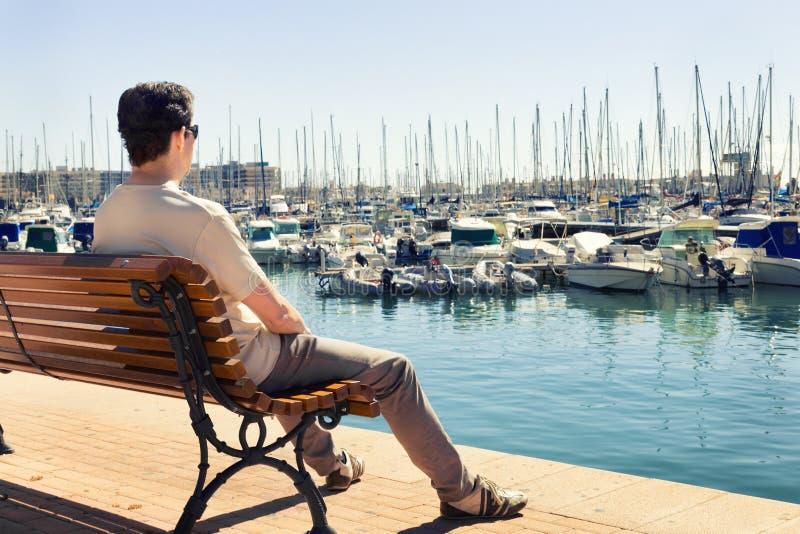 Homme contemplant les bateaux dans le port maritime photographie stock