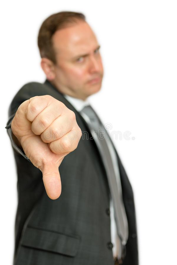 Homme contrarié et fâché d'affaires donnant des pouces vers le bas image stock