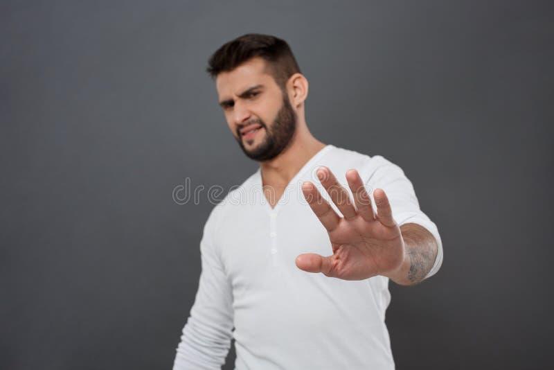 Homme contrarié refusant, étirant la main à l'appareil-photo au-dessus du fond gris photo stock