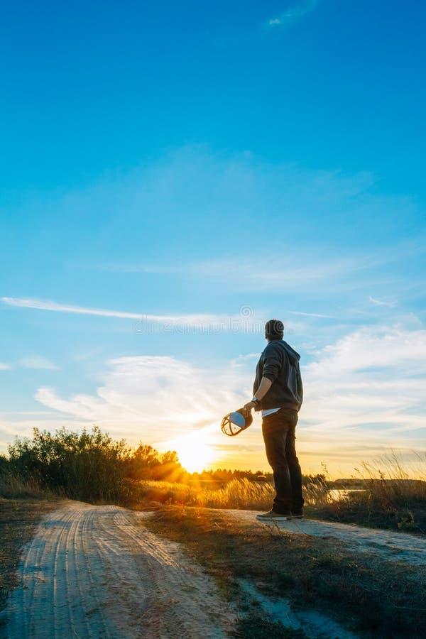 Homme contre le coucher du soleil dans un domaine sur la route images libres de droits