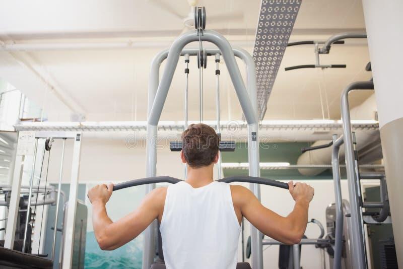Homme convenable à l'aide de la machine de poids pour des bras images stock