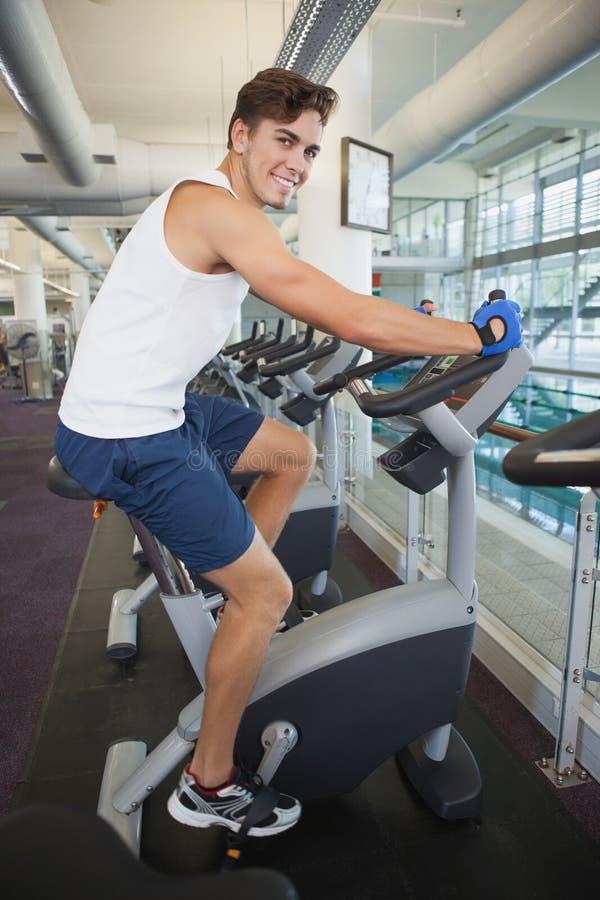 Homme convenable établissant sur le vélo d'exercice images libres de droits