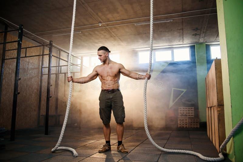 Homme convenable bel établissant avec des cordes de bataille au gymnase image stock