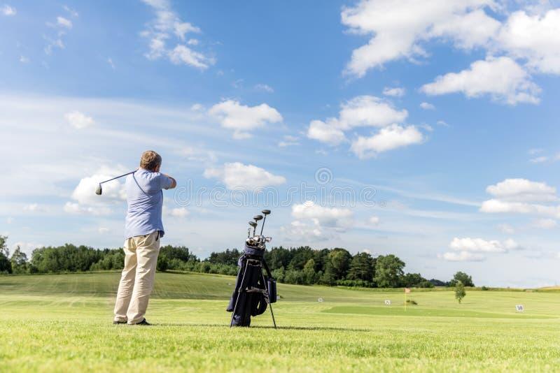 Homme convenable d'aîné frappant une boule de golf photo stock