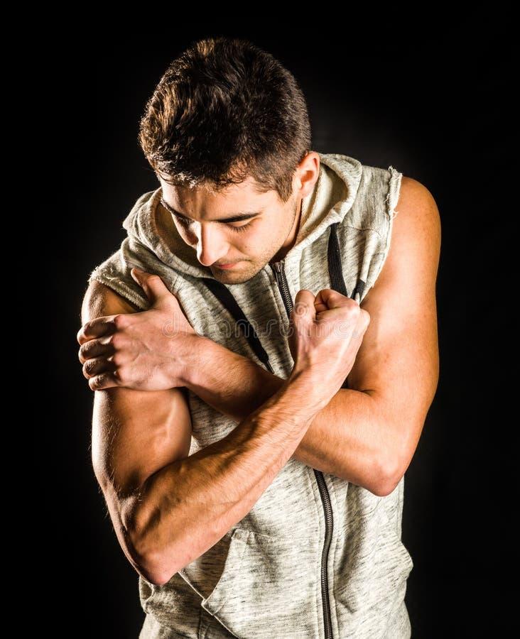 Homme convenable de jeunes fléchissant son biceps d'isolement sur le fond noir images stock