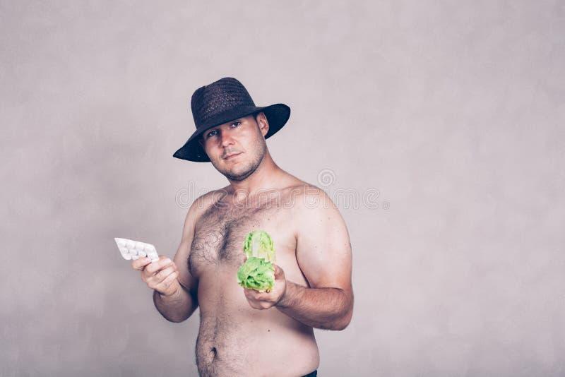 Homme corpulent nu tenant les pharmaceutiques et le légume photographie stock libre de droits