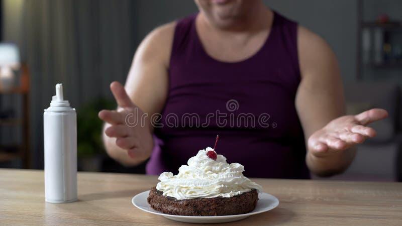 Homme corpulent regardant le gâteau de chocolat avec la crème fouettée, nourriture malsaine photos libres de droits