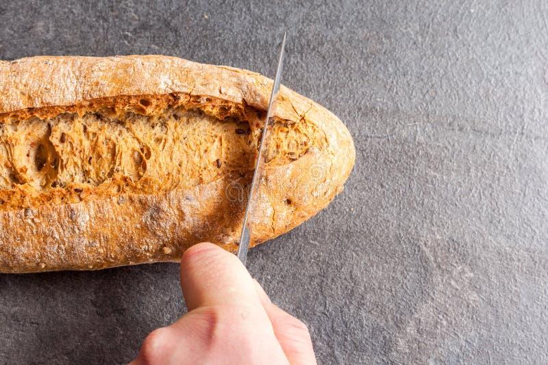 Homme coupant un pain photo libre de droits