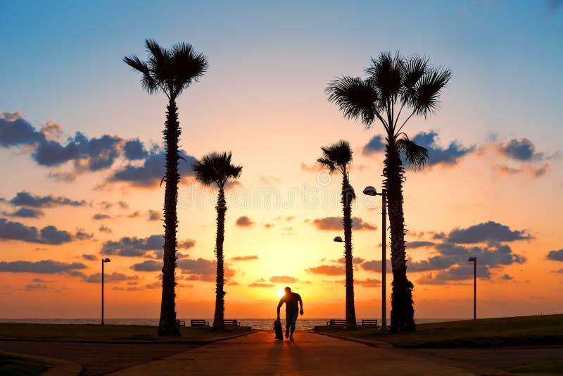 Homme courant avec la planche à roulettes dans le coucher du soleil photo stock