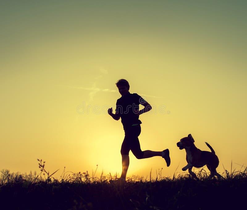 Homme courant avec ses silhouettes de coucher du soleil de chien photographie stock libre de droits