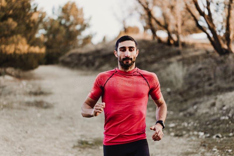 Homme courant de sport dans la course de traînée de pays croisé Formation masculine convenable d'exercice de coureur et sauter de image stock