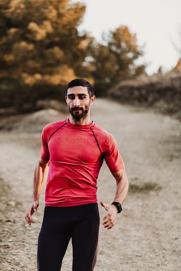 Homme courant de sport dans la course de traînée de pays croisé Formation masculine convenable d'exercice de coureur et sauter de photographie stock