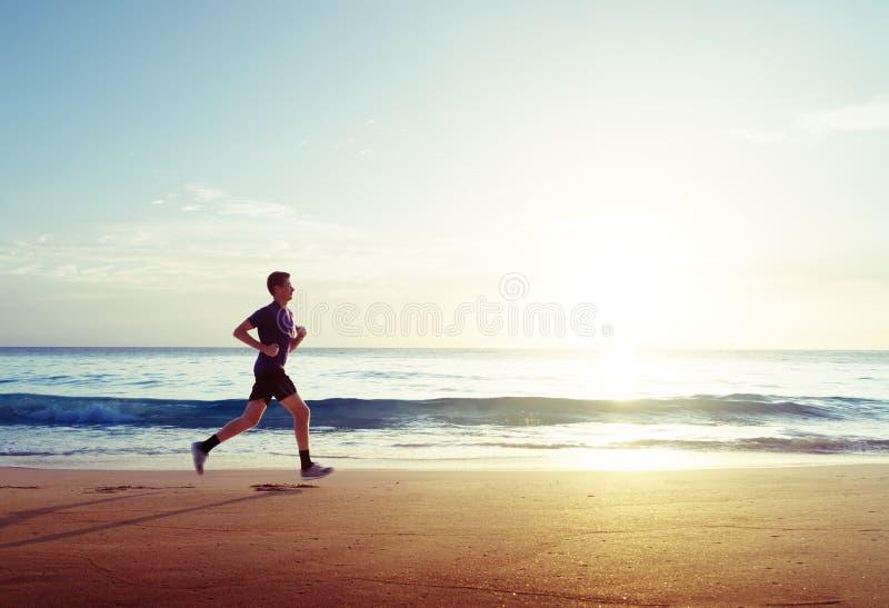 Homme courant sur la plage tropicale au coucher du soleil images stock