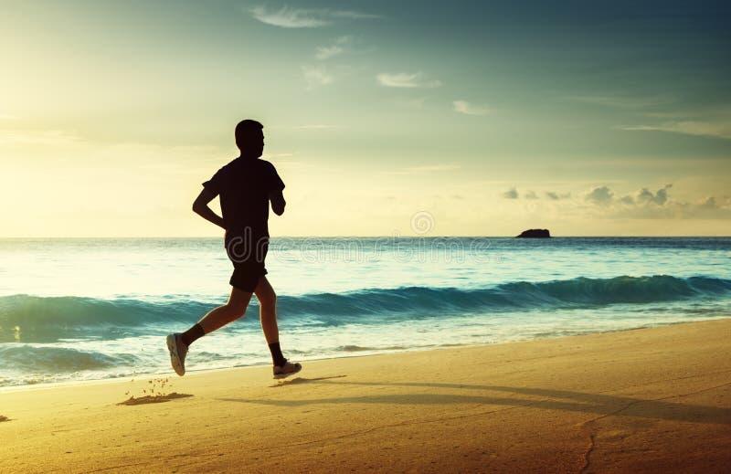 Homme courant sur la plage tropicale au coucher du soleil photographie stock