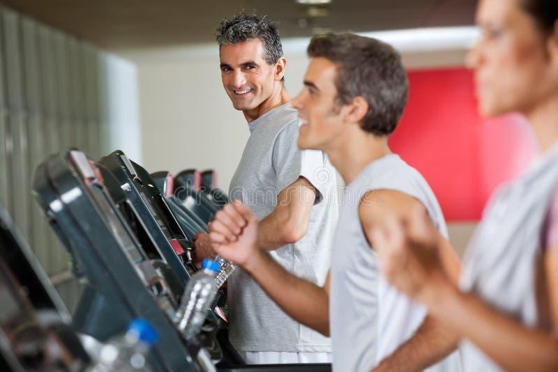 Homme courant sur le tapis roulant dans le centre de fitness photographie stock libre de droits