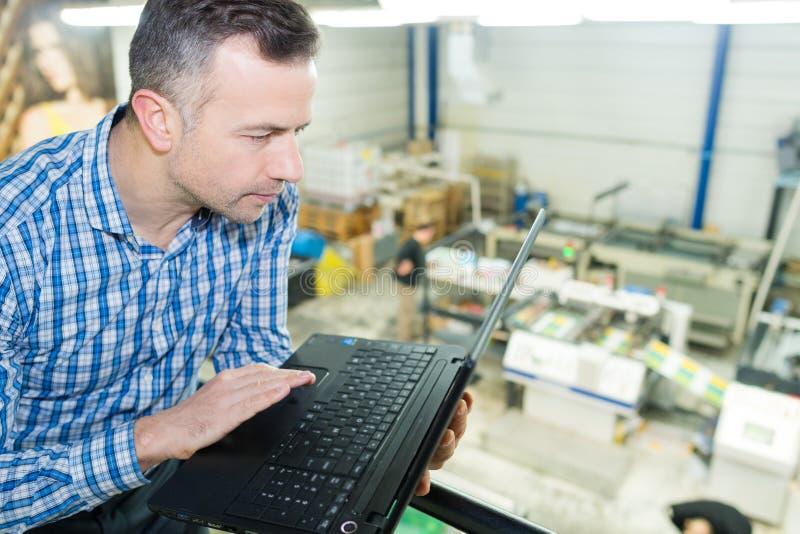 Homme courbe de vue utilisant l'ordinateur portable au-dessus des travaux d'impression images libres de droits