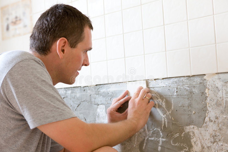 Homme couvrant de tuiles un mur photo stock