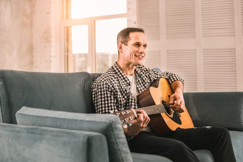 Homme créatif désireux maîtrisant sa guitare jouant des qualifications image libre de droits