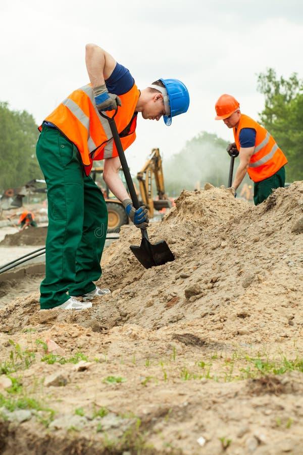 Homme creusant à la construction de routes photographie stock libre de droits