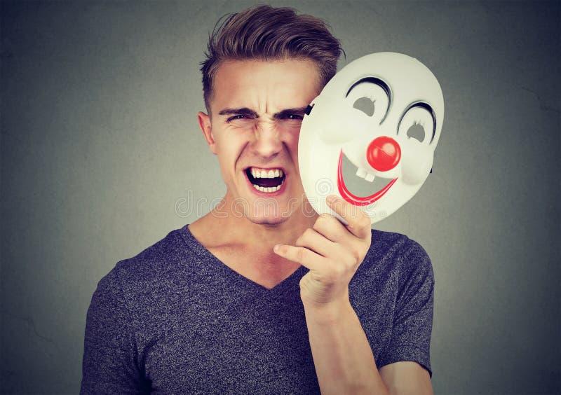 Homme criard fâché de portrait enlevant un masque de clown exprimant le bonheur photo stock