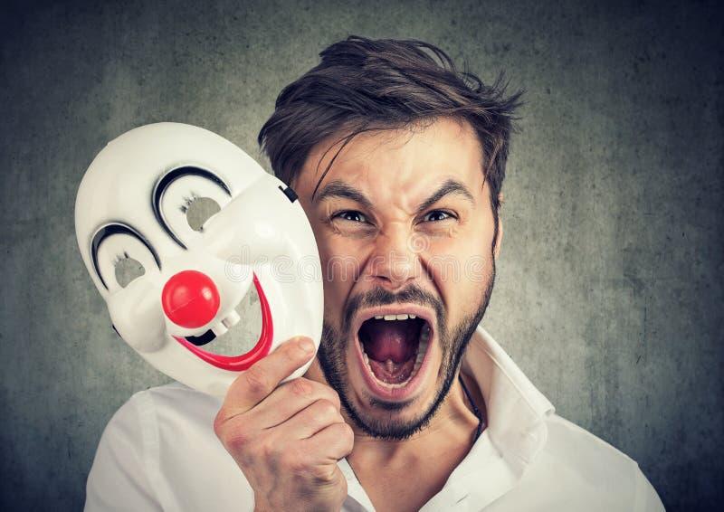 Homme criard fâché enlevant un masque de clown images stock