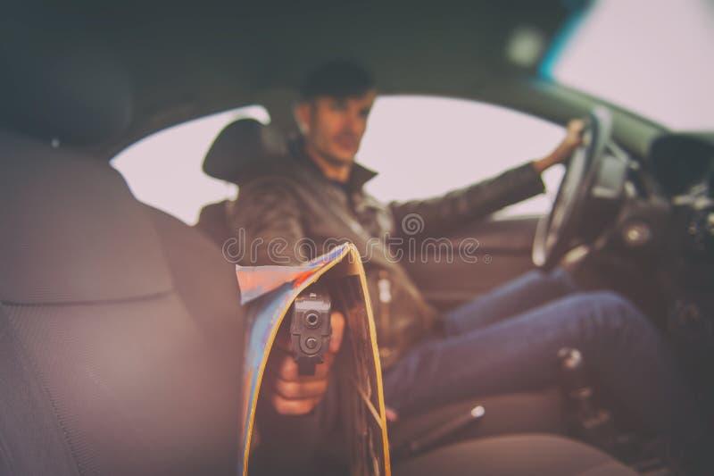 Homme criminel avec une arme à feu se reposant dans la voiture photographie stock libre de droits