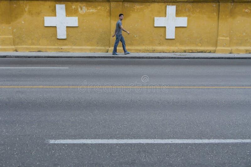 Homme cubain marchant le long du mur de jaune de cimetière de deux points à La Havane images stock