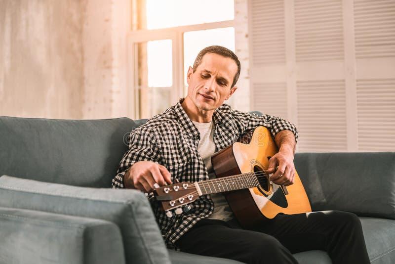 Homme curieux assidu travaillant dur pour réaliser le progrès sur ses qualifications de guitare photographie stock