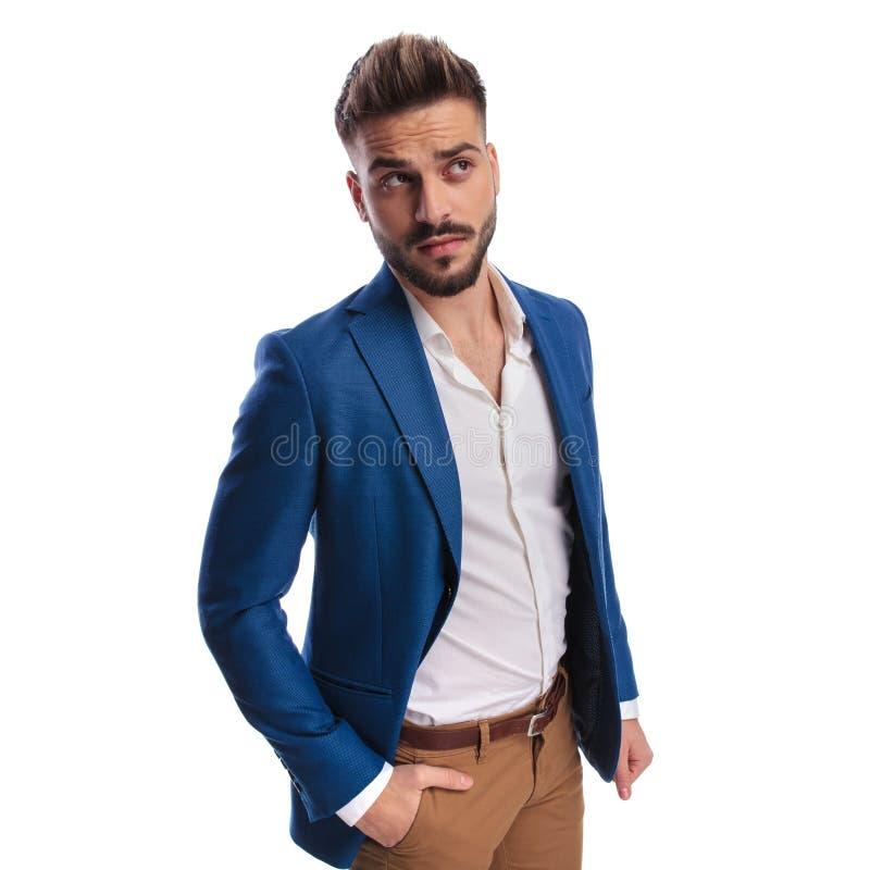 Homme curieux dans le costume recherchant avec la main dans la poche photo stock