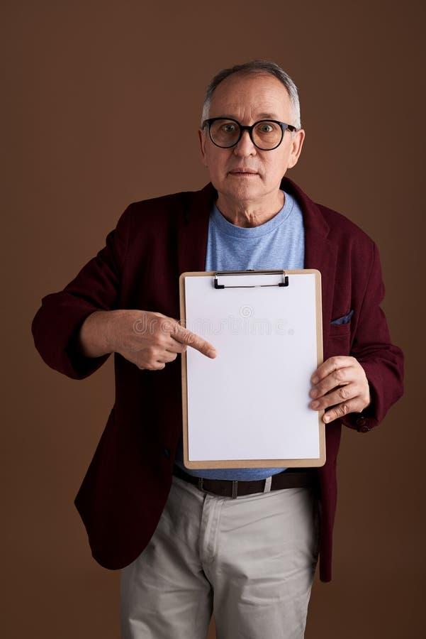 Homme curieux indiquant la feuille de papier et semblant étonné photographie stock