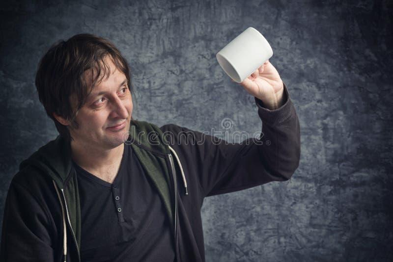 Homme déçu regardant la tasse vide image stock