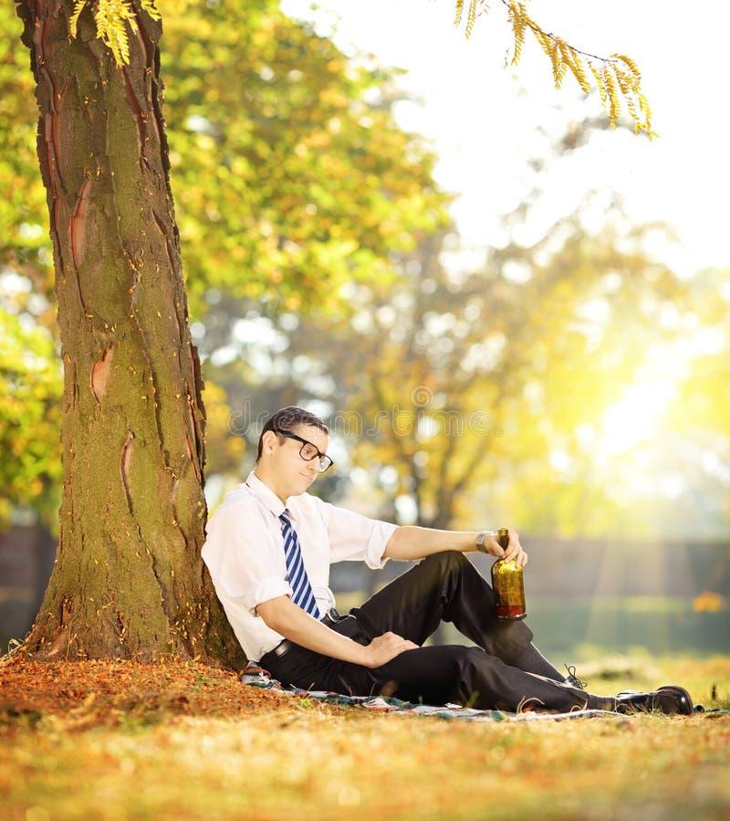 Homme déçu s'asseyant sur une herbe avec la bouteille dans sa main, dedans photo stock