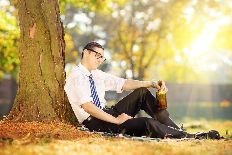 Homme déçu s'asseyant sur une herbe avec la bouteille dans sa main, dedans photographie stock