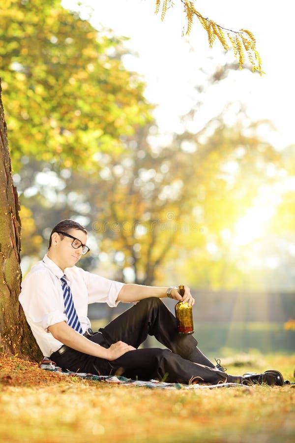 Homme déçu s'asseyant sur une herbe avec la bouteille en parc sur un soleil images libres de droits
