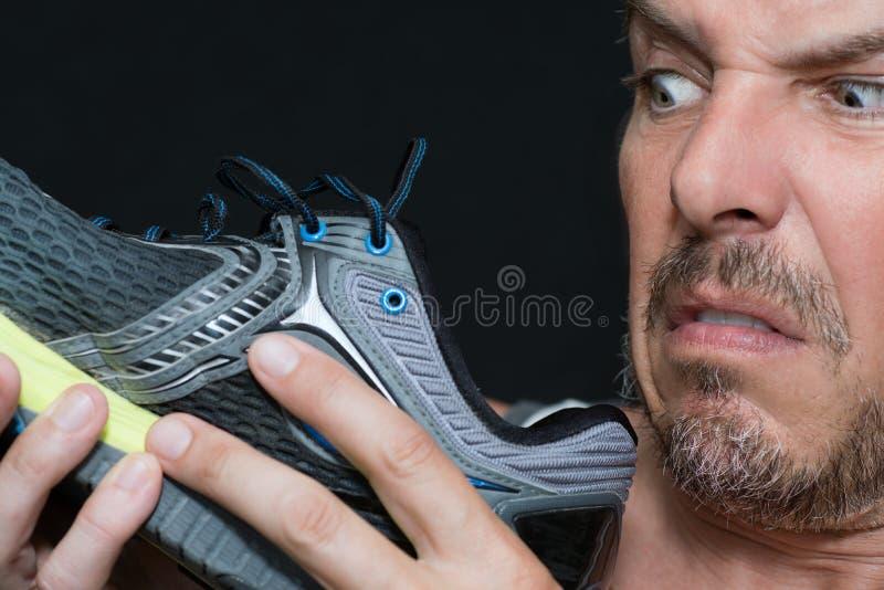 Homme dégoûté par l'odeur de chaussures image libre de droits