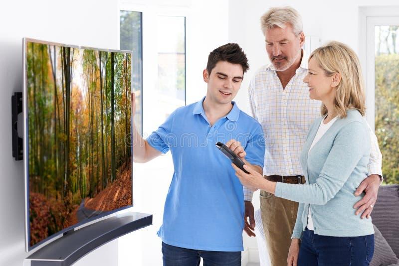 Homme démontrant la nouvelle télévision aux couples mûrs à la maison images libres de droits
