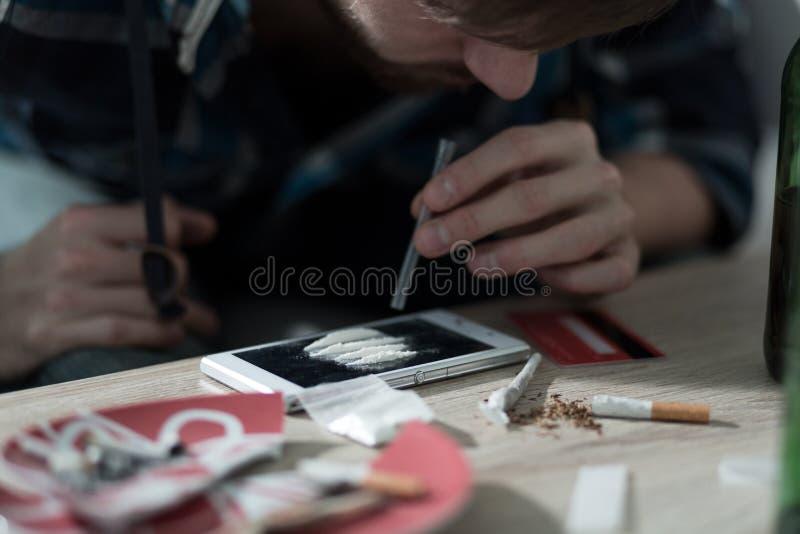 Homme dépendant de drogue prenant la cocaïne images stock