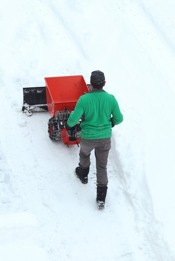 Homme déplaçant un chasse-neige motorisé image stock
