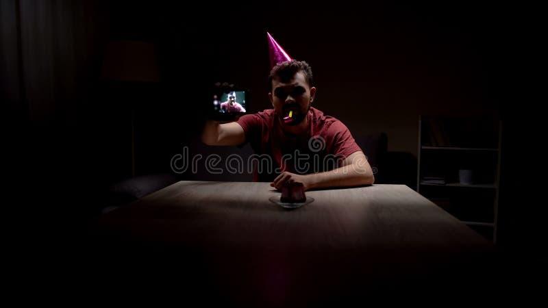 Homme déprimé célébrant seul l'anniversaire, faisant le selfie dans la chambre noire, malheureuse photo stock