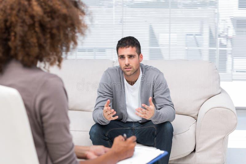 Homme déprimé parlant à un thérapeute image stock