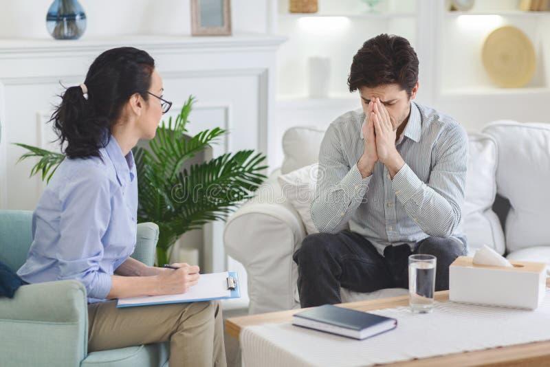 Homme déprimé parlant avec émotion à la session de psychothérapeute photographie stock libre de droits
