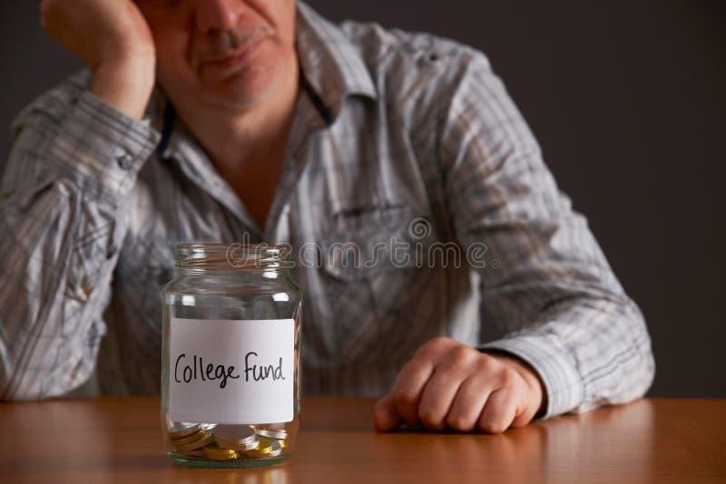 Homme déprimé regardant le pot vide marqué fonds d'université photo stock