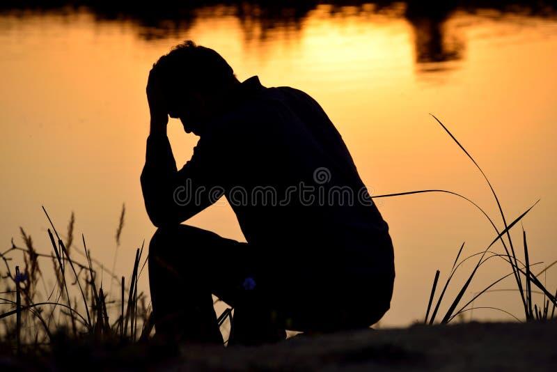Homme déprimé s'asseyant sur des mains images stock