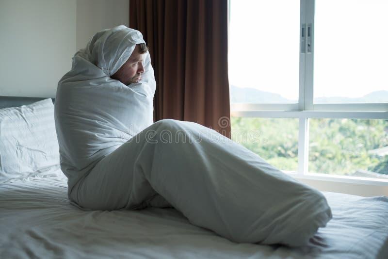 Homme déprimé s'asseyant sur son lit couvert de couverture et regardant la fenêtre Il est déprimé après divorce images libres de droits
